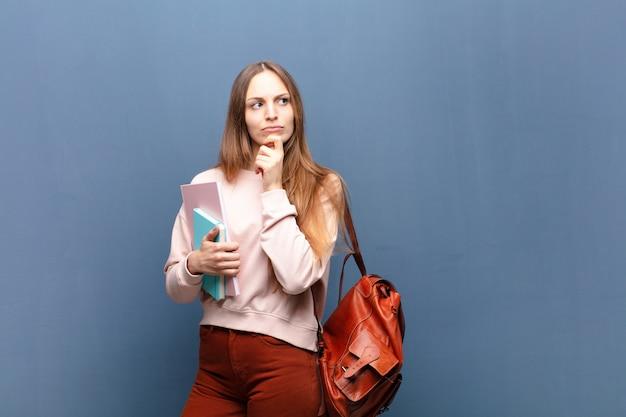 Giovane donna graziosa dello studente con i libri e la borsa contro la parete blu con uno spazio della copia Foto Premium