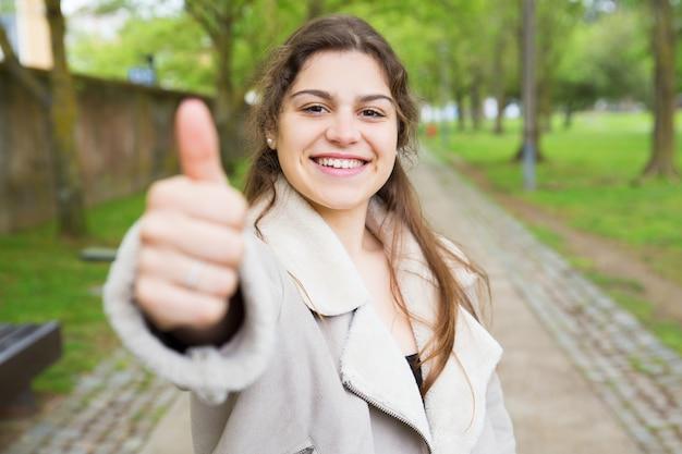 Giovane donna graziosa felice che mostra pollice su nel parco Foto Gratuite