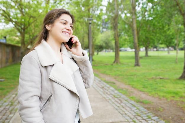 Giovane donna graziosa felice che rivolge allo smartphone in parco Foto Gratuite