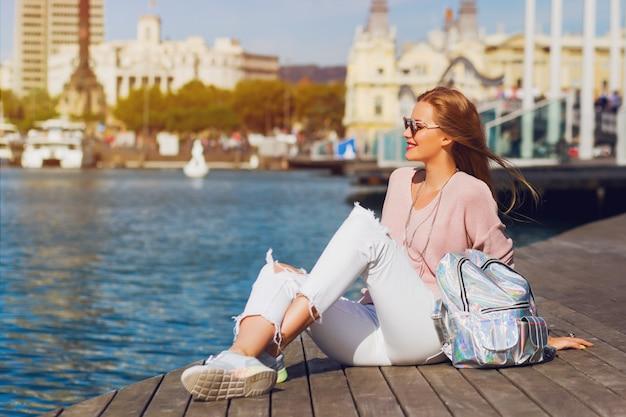 Giovane donna graziosa fresca che si siede sul pilastro di legno vicino al mare e che esamina la città. ragazza attraente dei pantaloni a vita bassa con lo zaino che gode delle sue vacanze concetto attivo di stile di vita. Foto Gratuite