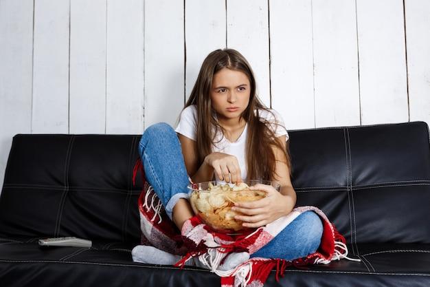 Giovane donna graziosa, guardare la tv, seduto sul divano di casa. Foto Gratuite