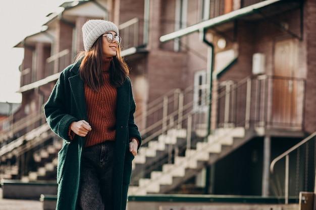 Giovane donna graziosa in cappotto caldo vicino alla casa Foto Gratuite