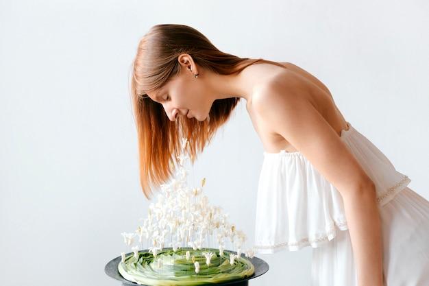 Giovane donna graziosa in composizione sentente l'odore nel mazzo della molla del fiore del vestito greco bianco da stile dell'interno. Foto Premium