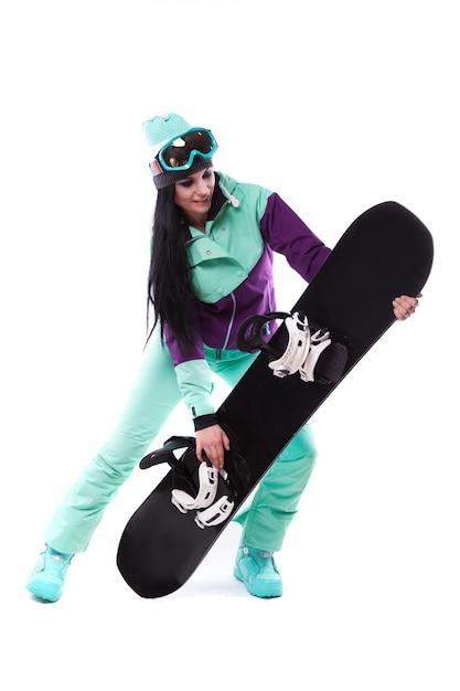 Giovane donna graziosa in snowboard viola della stretta del costume dello sci Foto Premium