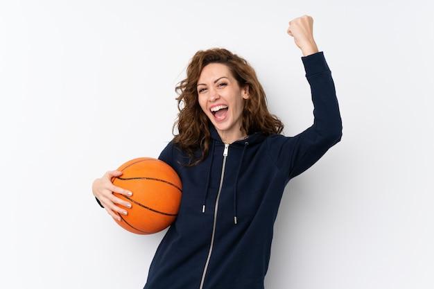 Giovane donna graziosa sopra isolata con la palla di pallacanestro Foto Premium
