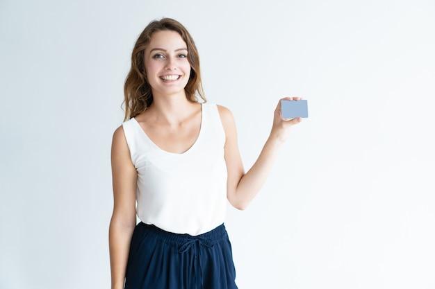 Giovane donna graziosa sorridente che mostra biglietto da visita in bianco Foto Gratuite