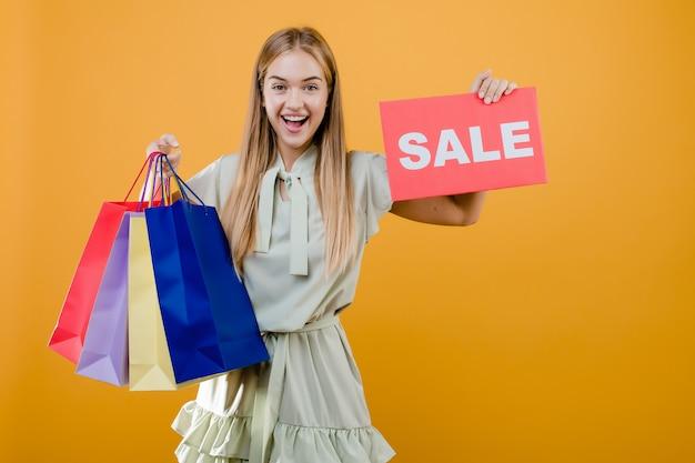 Giovane donna graziosa sorridente felice con il segno di vendita e sacchetti della spesa variopinti isolati sopra giallo Foto Premium