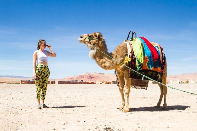 Giovane donna guardando un cammello nel deserto Foto Gratuite