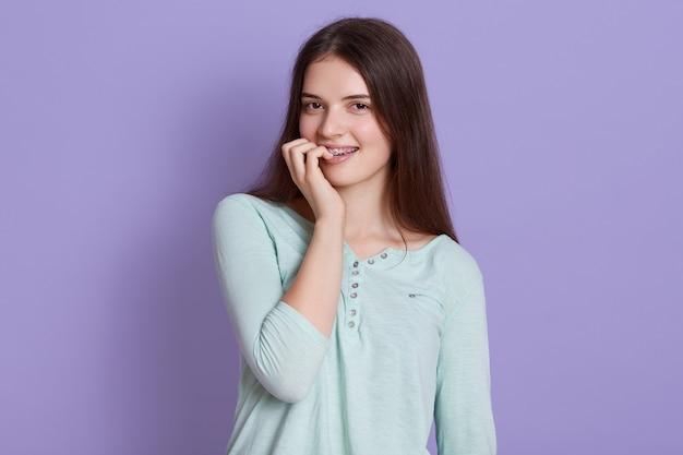 Giovane donna hared scura che porta camicia casuale che esamina macchina fotografica e che morde le sue dita Foto Gratuite