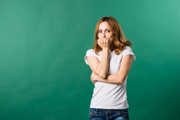 Giovane donna impaurita che copre la sua bocca contro il contesto verde Foto Gratuite
