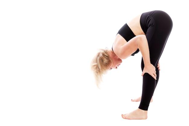 Giovane donna in abbigliamento nero fitness facendo stretching mentre in piedi. isolato su sfondo bianco. spazio per il testo. Foto Premium
