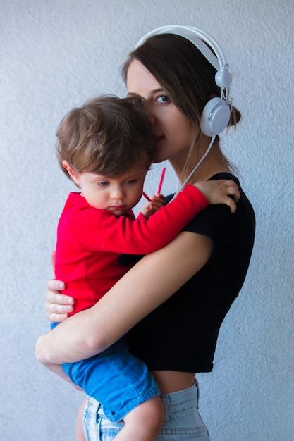 Giovane donna in abiti stile cappello e anni '90 e piccolo bambino ragazzo Foto Premium