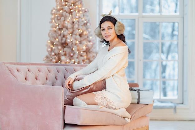 Giovane donna in abito bianco sul divano nel periodo natalizio Foto Gratuite