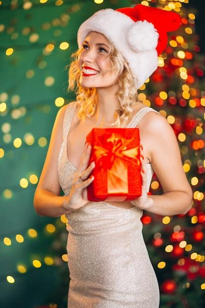 Giovane donna in abito con regali di natale di albero di natale Foto Gratuite