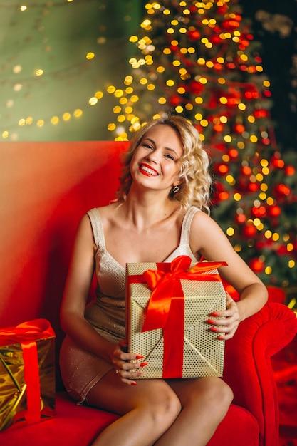 Giovane donna in abito con regali di natale seduto sul divano Foto Gratuite