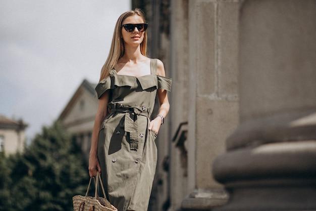 Giovane donna in abito verde in piedi dal vecchio edificio Foto Gratuite
