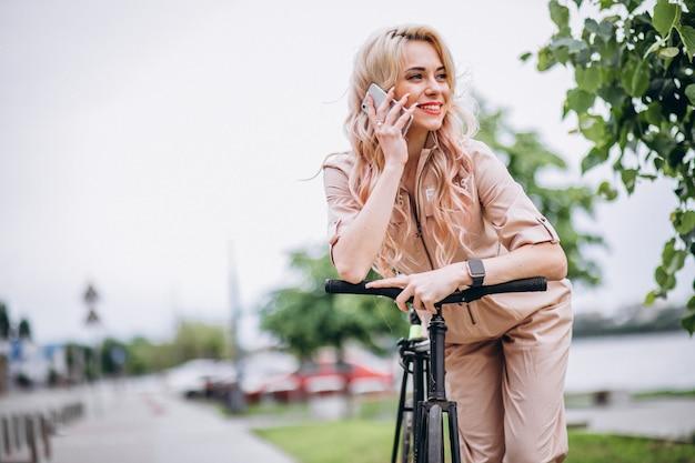 Giovane donna in bicicletta nel parco Foto Gratuite