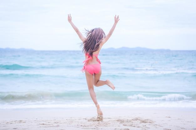 Giovane donna in bikini che salta sulla spiaggia di sabbia e onde e relax, concetto di viaggio estivo. Foto Premium