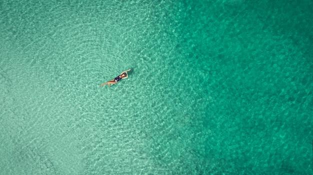 Giovane donna in bikini sdraiato sulla schiena sulla sabbia bianca vicino alle onde del mare blu Foto Premium