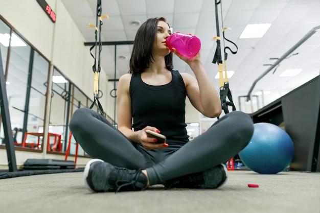 Giovane donna in buona salute con acqua di bottiglia che riposa in ginnastica Foto Premium