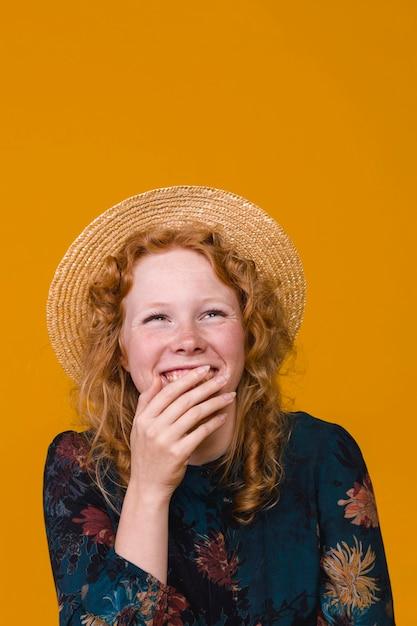 Giovane donna in cappello che ride e che copre la bocca Foto Gratuite