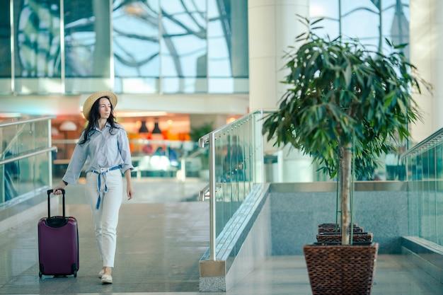 Giovane donna in cappello con bagaglio in aeroporto internazionale. Foto Premium
