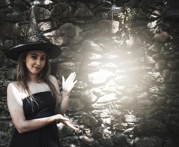 Giovane donna in cappello della strega che sta vicino al punto ... 46241dab5143