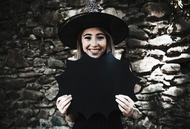 Giovane donna in cappello della strega che tiene decorazione e sorridere di  Halloween Foto Gratuite c3e8fe9a25d2