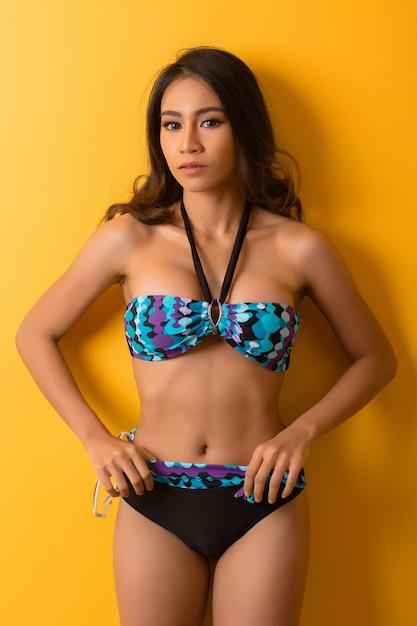 Giovane donna in costume da bagno isolato su giallo Foto Gratuite