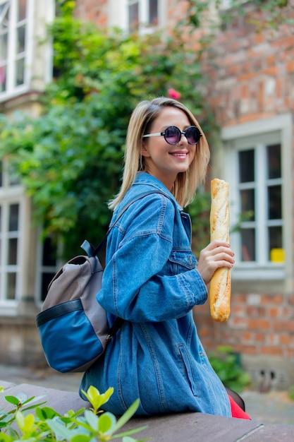 Giovane donna in giacca di jeans sulla strada medievale di brema Foto Premium