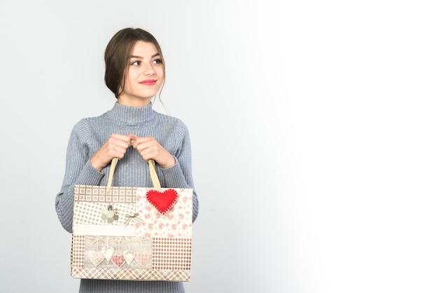 Giovane donna in piedi con la borsa regalo Foto Gratuite