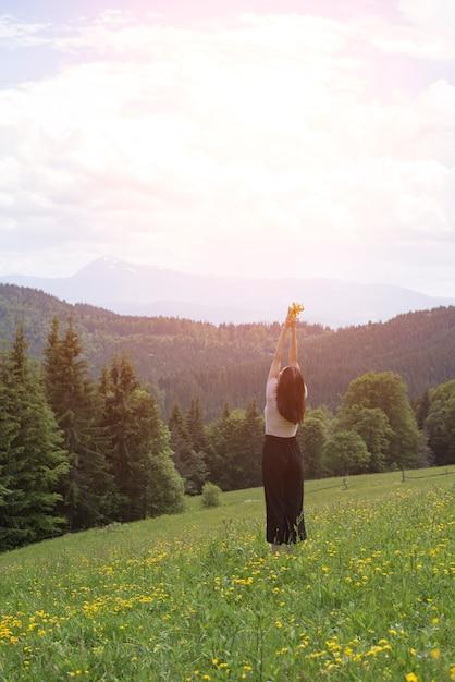 Giovane donna in piedi con un mazzo di fiori e mani sollevate Foto Premium