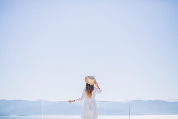 Giovane donna in piedi da dietro e guardando il mare Foto Gratuite