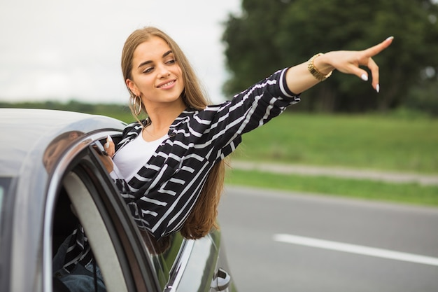Giovane donna in piedi fuori dal finestrino della macchina che punta a qualcosa Foto Gratuite