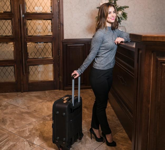 Giovane donna in piedi vicino alla reception con la valigia in hotel Foto Gratuite