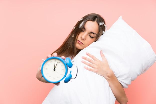 Giovane donna in pigiama che tiene orologio vintage Foto Premium