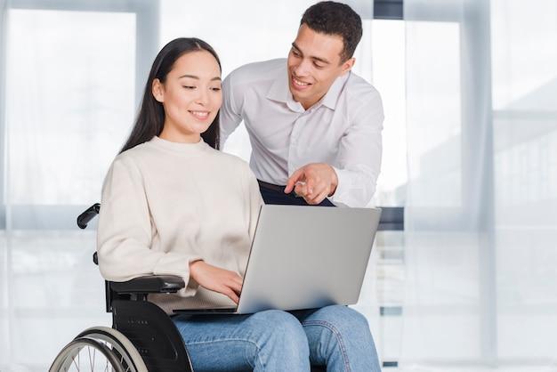 Giovane donna in sedia a rotelle, lavorando con un collega di sesso maschile Foto Gratuite