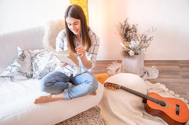 Giovane donna in soggiorno con una chitarra. Foto Gratuite