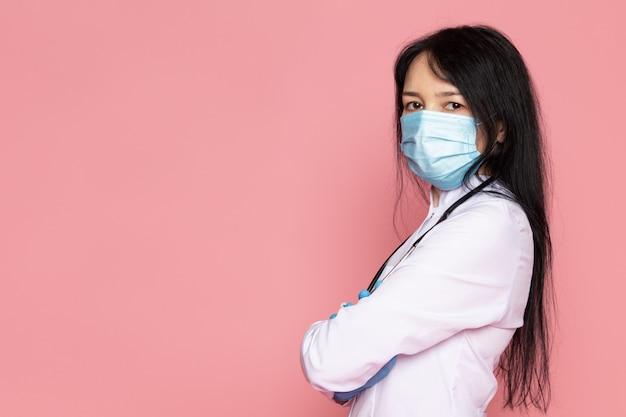Giovane donna in tuta medica bianco guanti blu maschera protettiva blu sul rosa Foto Gratuite