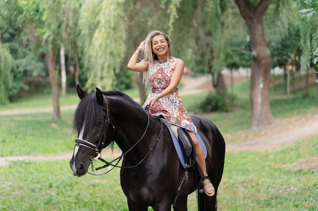 Giovane donna in un abito colorato luminoso a cavallo nero Foto Gratuite