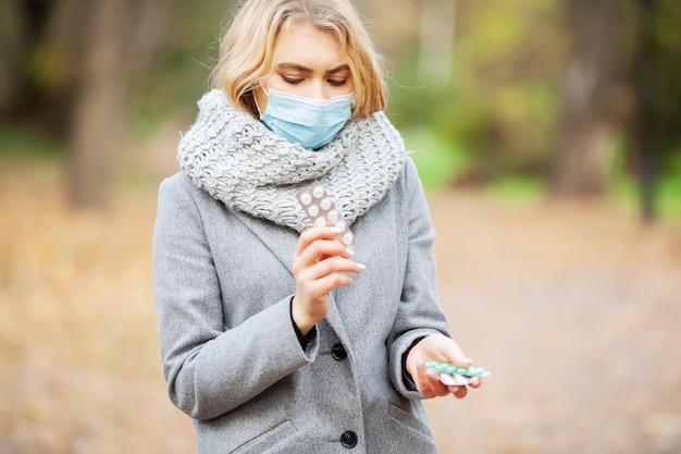 Giovane donna in un cappotto grigio che cammina nel parco di autunno con una maschera Foto Premium