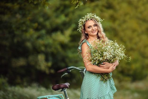 Giovane donna in un vestito con una bici e un mazzo di fiori di campo Foto Premium