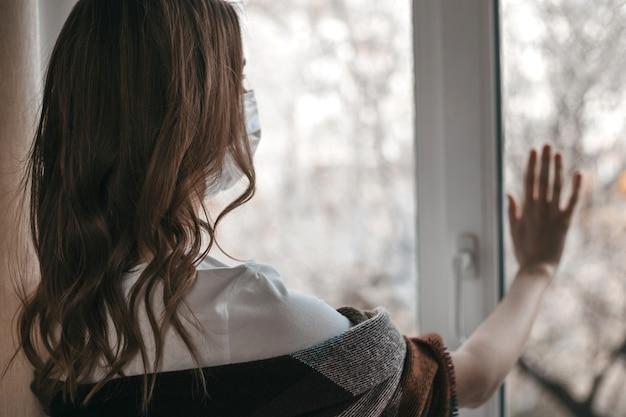 Giovane donna in una maschera medica guarda fuori dalla finestra e tiene la mano sul vetro della finestra, quarantena, isolamento, coronavirus, sta al sicuro a casa, Foto Premium