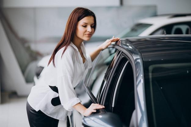 Giovane donna in una sala d'esposizione dell'automobile che sceglie un'automobile Foto Gratuite