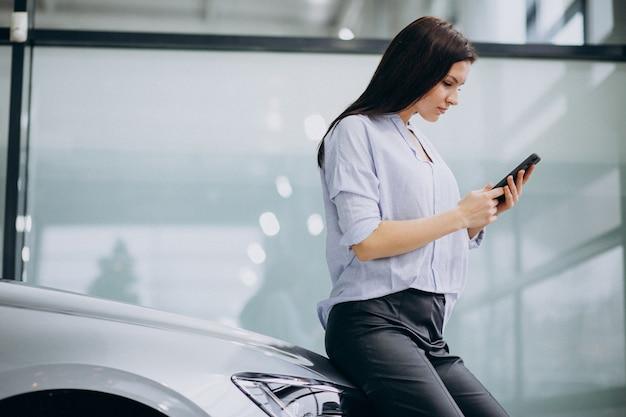 Giovane donna in una sala di show car utilizzando il telefono Foto Gratuite