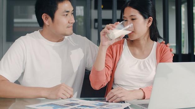 Giovane donna incinta asiatica che usando le annotazioni del computer portatile delle entrate e delle spese a casa. papà che dà il latte a sua moglie mentre registra un bilancio, una tassa, un documento finanziario che lavora nel salotto di casa la mattina Foto Gratuite