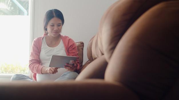 Giovane donna incinta asiatica che usando le informazioni di gravidanza di ricerca della compressa. la mamma si sente felice sorridente positivo e pacifico mentre si prende cura del suo bambino sdraiato sul divano nel salotto di casa. Foto Gratuite