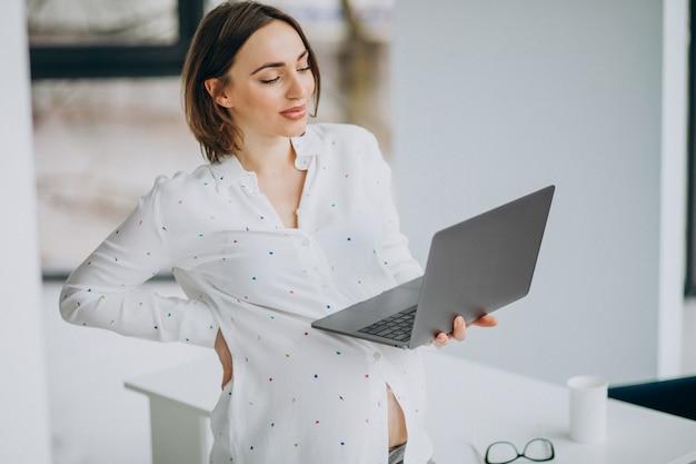 Giovane donna incinta che lavora al computer fuori dall'ufficio Foto Gratuite