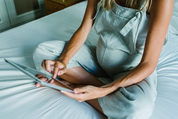 Giovane donna incinta che per mezzo di una compressa digitale mentre riposando sul letto a casa Foto Premium