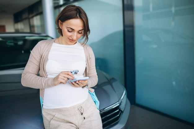 Giovane donna incinta che sceglie un'automobile in una sala d'esposizione dell'automobile Foto Gratuite